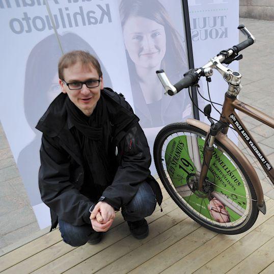 Leo Stranius oman vaalipyöränsä vieressä ja Outi Alanko-Kahiluodon ja Tuuli Kousan vaalijulisteiden edessä.