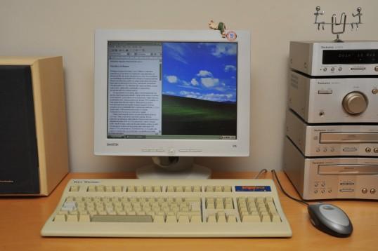 """Pöydällä näyttö, stereot, näppäimistö, hiiri ja kaiutin. Näytöllä Windows XP:n työpöytä ja Wordpad-ohjelma, jossa teksti """"Kierrätys on ilomme"""". Stereon näytössä näkyy teksti """"Doin' it Rig""""."""