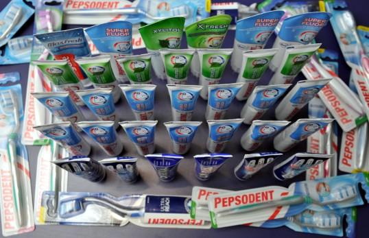 33 hammastahnaputkiloa pystyssä hammasharjapakkausten ympäröiminä.