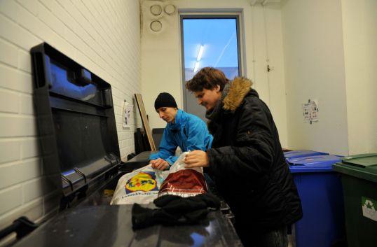 Onni Tonkija ja Roope Salminen tutkivat roskapussien sisältöä jätehuoneessa.