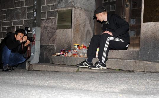 Sami Kero valokuvaa HEO-kansanopiston portailla dyykkisaaliinsa vieressä istuvaa Onni Tonkijaa.
