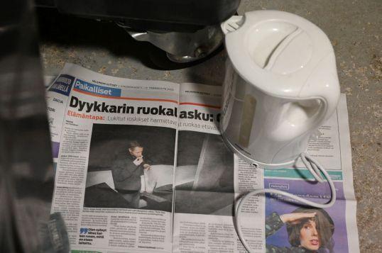 Helsingin Uutiset auki dyykkarijutun kohdalta jätekatoksen lattialla vedenkeittimen alla.