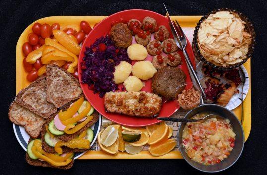 Keltaisella tarjottimella pikkutomaatteja, suikaloitua paprikaa, lämpimiä juustoleipiä, kurkku-paprika-maksamakkararuisleipiä, appelsiini- ja limettilohkoja, lautasellinen broilerikeittoa, paahdettua sipulia, marjapiirakkaa, sileitä ja poimutettuja perunalastuja, lihapullia ja ketsuppia, lihamurekepihvi, keitettyjä perunoita, punakaalisalaattia ja liha-makaronilaatikkoa.