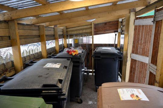 Jätekatoksessa vieri vieressä roska-astioita, joista yhden päällä on klementiinejä, palanen paprikaa ja leipäpussi.