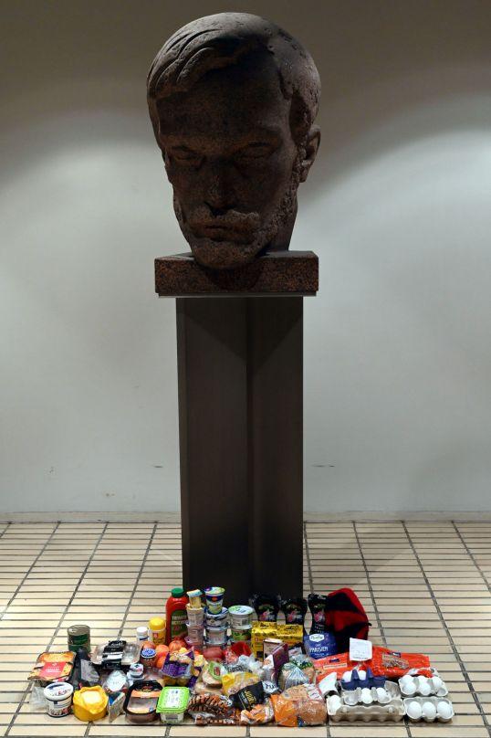 Elintarvikkeita aseteltuna Wäinö Aaltosen veistämän Aleksis Kiveä esittävän patsaan eteen.
