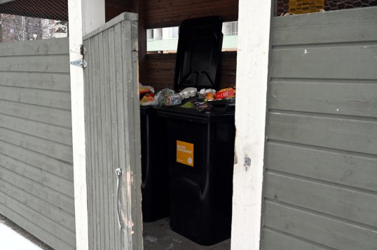 Lankahaalla varustettu jätekatoksen ovi sulkeutumassa. Taustalla pieni sekajäteastia, jossa on kartonkipakkauksia, sekä pieni muovinkeräysastia, jonka päällä on kananmunia, paahtoleipää, lasagnea ja metvurstia.