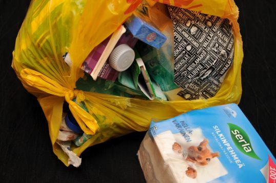 Auki repäistyssä muovikassissa muun muassa avaamattomat pakkaukset marjakeittoa, purukumia ja pastilleja. Kassin ulkopuolella paketti nenäliinoja.