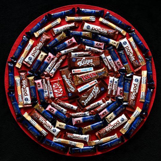 Ympyrän muotoisessa asetelmassa 67 suklaapatukkaa ja 11 lakritsipatukkaa.