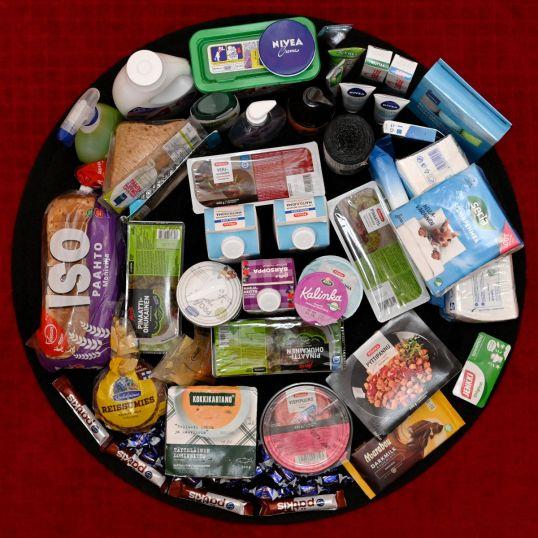 Ympyrän muotoisessa asetelmassa muun muassa suklaata, valmisruokia, leipää, maitotuotteita, pesuaineita, puhdistusliinoja, roskapusseja ja nenäliinoja.
