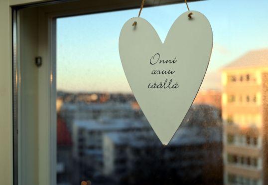 """Ikkunassa valkoinen sydän, jossa lukee """"Onni asuu täällä""""."""