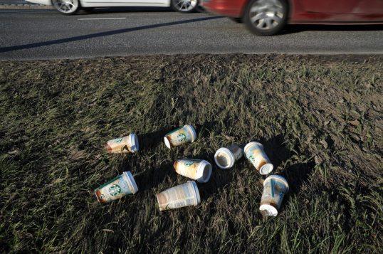 Kahdeksan Starbucks-maitokahvijuomapurkkia pientareella ohi kulkevien autojen vieressä.