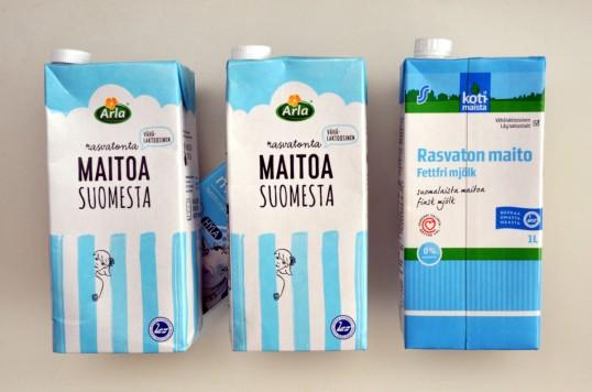 Kolme maitotölkkiä, joiden takana neljännessä maitotölkissä näkyy lehmän kuva.