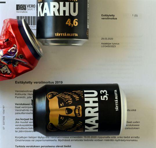 Esitäytetyn veroilmoituksen päällä kaksi Karhu-oluttölkkiä ja rytistetty Koff-tölkki.