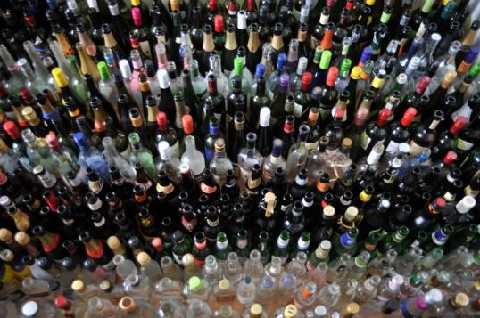 Suuri määrä erivärisiä ja -muotoisia lasipulloja ylhäältä päin kuvattuna.