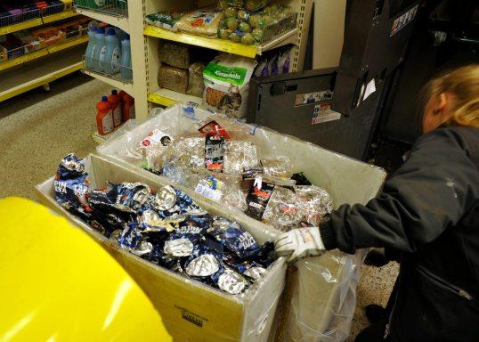 Panttiautomaatin täydet tölkki- ja pullosäiliöt esiin vedettyinä lähikaupassa.