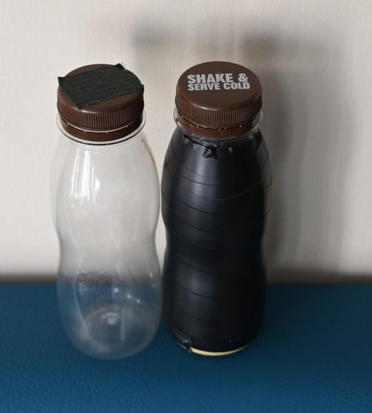 Kaksi pientä muovipulloa. Toisessa ei ole etikettiä, ja korkin päällä on musta teippi. Toinen on ympäröity täysin mustalla teipillä, mutta korkin teksti on näkyvissä.
