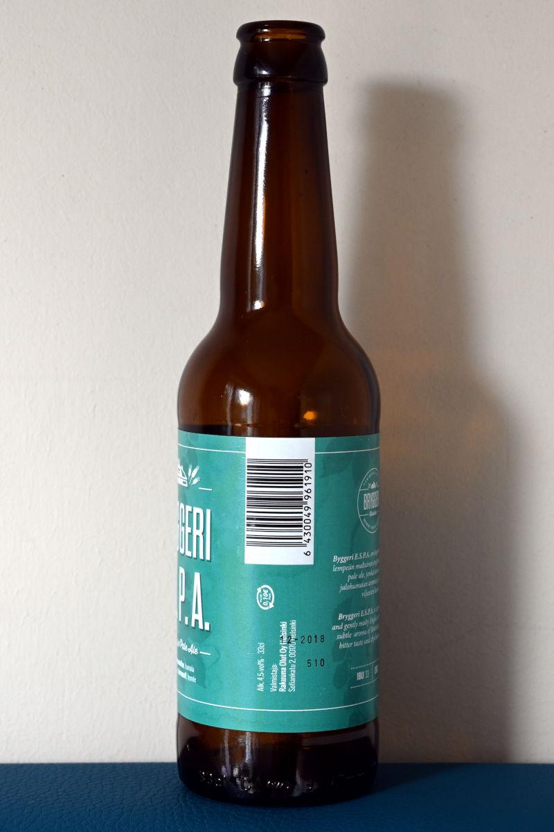 Bryggeri E. S. P. A. -olutpullossa hyvin pieni suomalainen panttimerkki isohkon tyhjän tilan ympärillä.