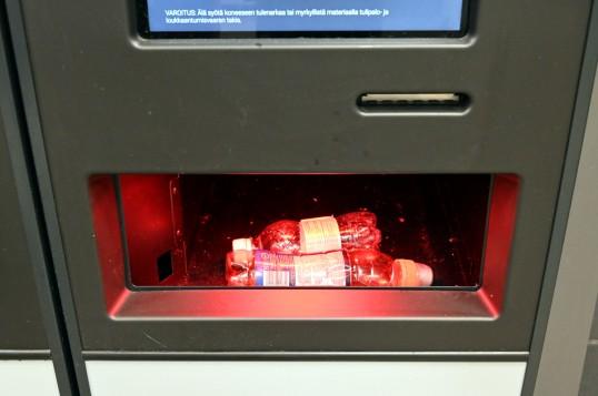 Pieni ja keskikokoinen muovipullo Tomra R1 -automaatin palautusluukussa.