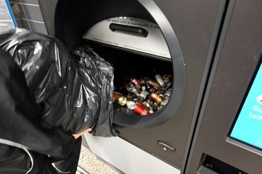 Tölkkejä ja pulloja kaadetaan jätesäkistä Tomra R1 -palautusautomaattiin.