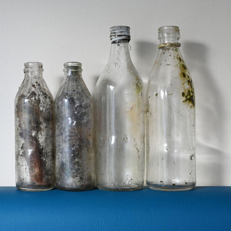 Neljä metsästä löytynyttä likaista ja etiketitöntä lasipulloa.