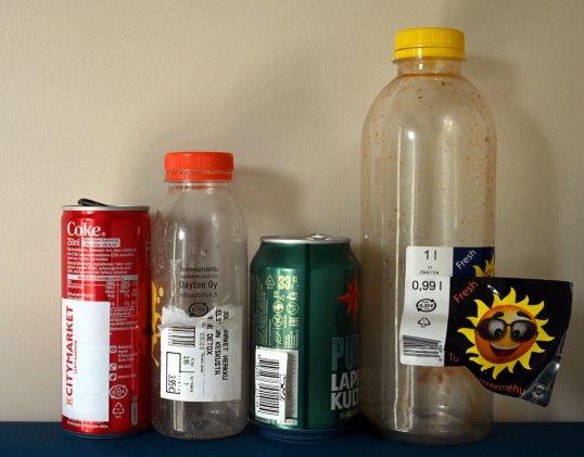 Kaksi juomatölkkiä ja kaksi muovipulloa, joiden alkuperäinen viivakoodi on peitetty tarralla.