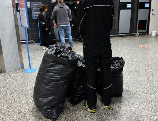 Pullonpalauttajia jätesäkkien kanssa palautusautomaattien edessä.