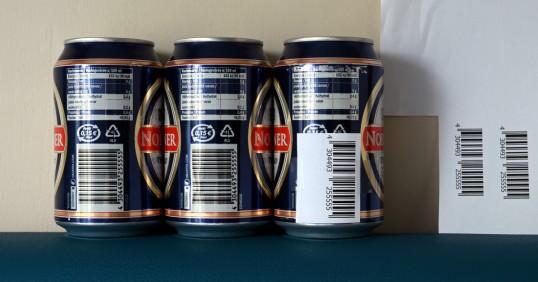 Kolme oluttölkkiä, joista yhteen on teipattu viereisestä arkista leikattu viivakoodi.