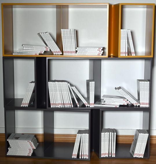 Sata Havahtuminen-kirjaa Ligne Roset'n harmaissa ja sinapinkeltaisessa Cuts-kirjahyllyissä.