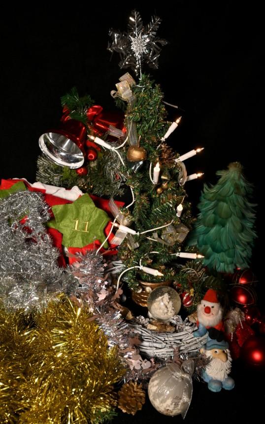 Pieni muovinen joulukuusi, jossa sähkökynttilät. Ympärillä nauhoja, palloja, kelloja ja muita joulukoristeita.