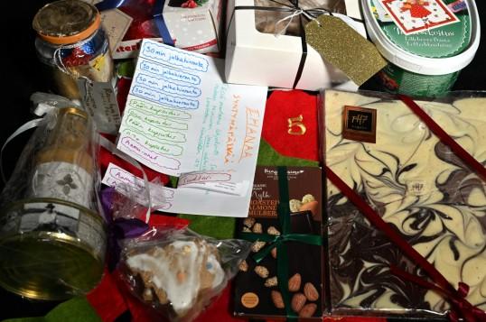 Suklaata, leivonnaisia ja muita elintarvikkeita lahjakääreissä. Lisäksi käsin paperille tehtyjä lahjakortteja.