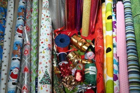 Joululahjapaperirullia ja muita lahjapaperirullia sekä lahjanauhoja, teippiä ja koristeruusukkeita.