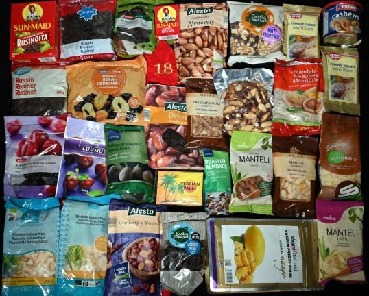 Rusinoita, kuivattuja sekahedelmiä, luumuja, viikunoita, taateleita, kookoslastuja, karpaloita, mangoja, manteleita, mantelilastuja, mantelijauheita, saksanpähkinöitä, parapähkinöitä ja cashewpähkinöitä pakkauksissaan.