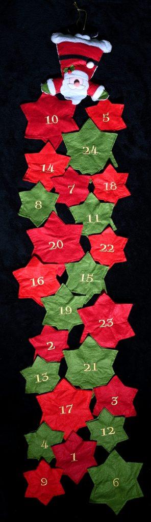 Huopainen pitkulainen joulukalenteri, jossa 24 numeroitua tähteä ja jonka päädyssä joulupukki.