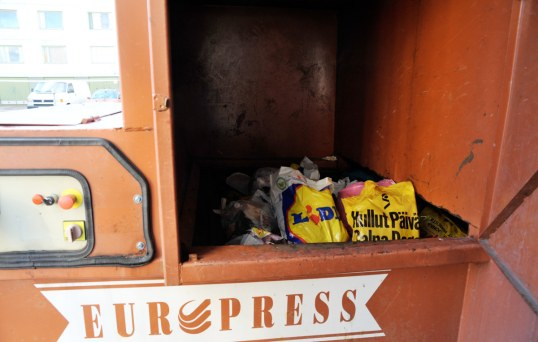 Jätepuristin, jonka avatusta luukusta näkyy roskapusseja.
