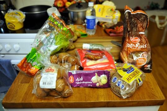 Pöydällä lehtisalaattia, leivonnaisia, kurkkua, juustoraastetta, majoneesiputkilo ja ruisleipää.