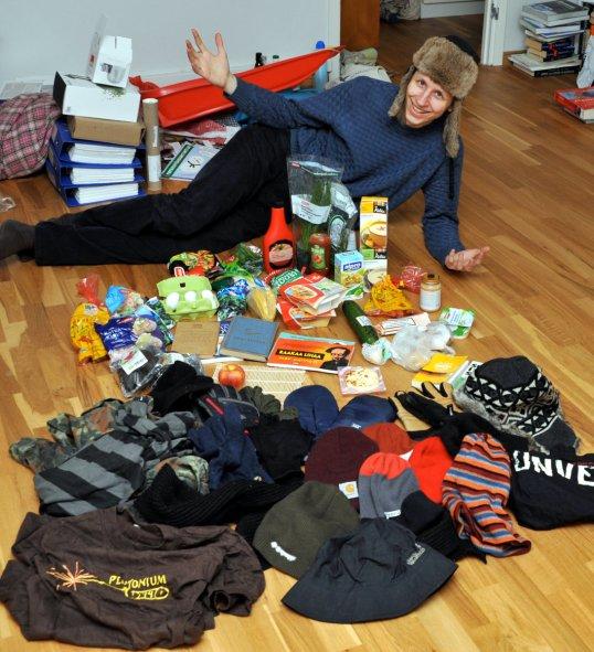 Onni Tonkija virnistää edessään ruokaa, kirjoja ja vaatteita.
