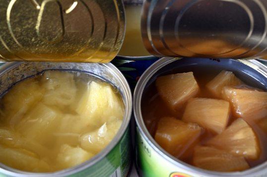 Keltaisia ananaspaloja tölkissä, jonka kiiltävässä metallisisuksessa on musta rengas. Toisessa tölkissä ruskehtavia ananaspaloja tölkissä, jonka sisusta on siniharmaa.