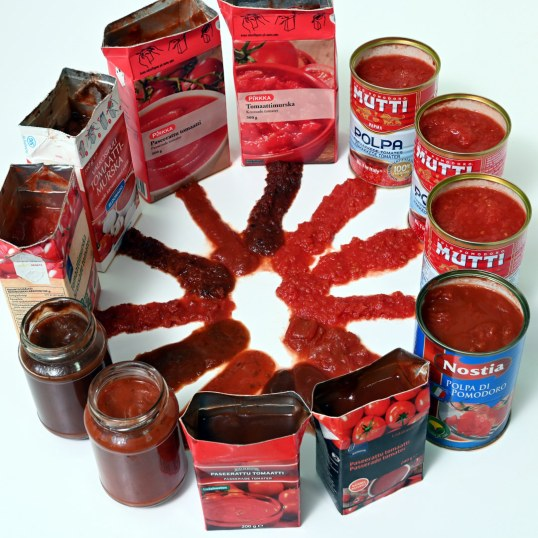 Erilaisia tomaattimurskasäilyketölkkejä ja -purkkeja ja niiden sisältöä valkoisella alustalla.