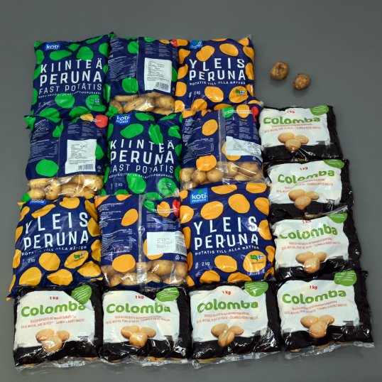 Lattialla seitsemän yhden kilon pussia ja yhdeksän kahden kilon pussia perunoita sekä kaksi yksittäistä perunaa.