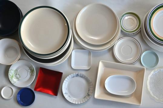 Erikokoisia, -muotoisia ja -värisiä lautasia, vateja ja kulhoja.