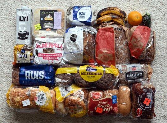 Toistakymmentä pussia leipää, tölkki kaurajuomaa, paketti broilerin fileepihvejä, rasia kananmunia, kaksi banaania, appelsiini ja pätkä kurkkua.
